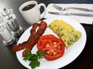 Image of a breakfast of lean bacon, tomato slices, and a zip-lock omelet.